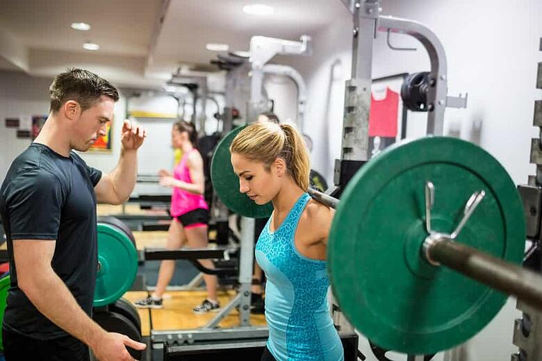Fit woman lifting heavy barbell in weights room at the gym_2