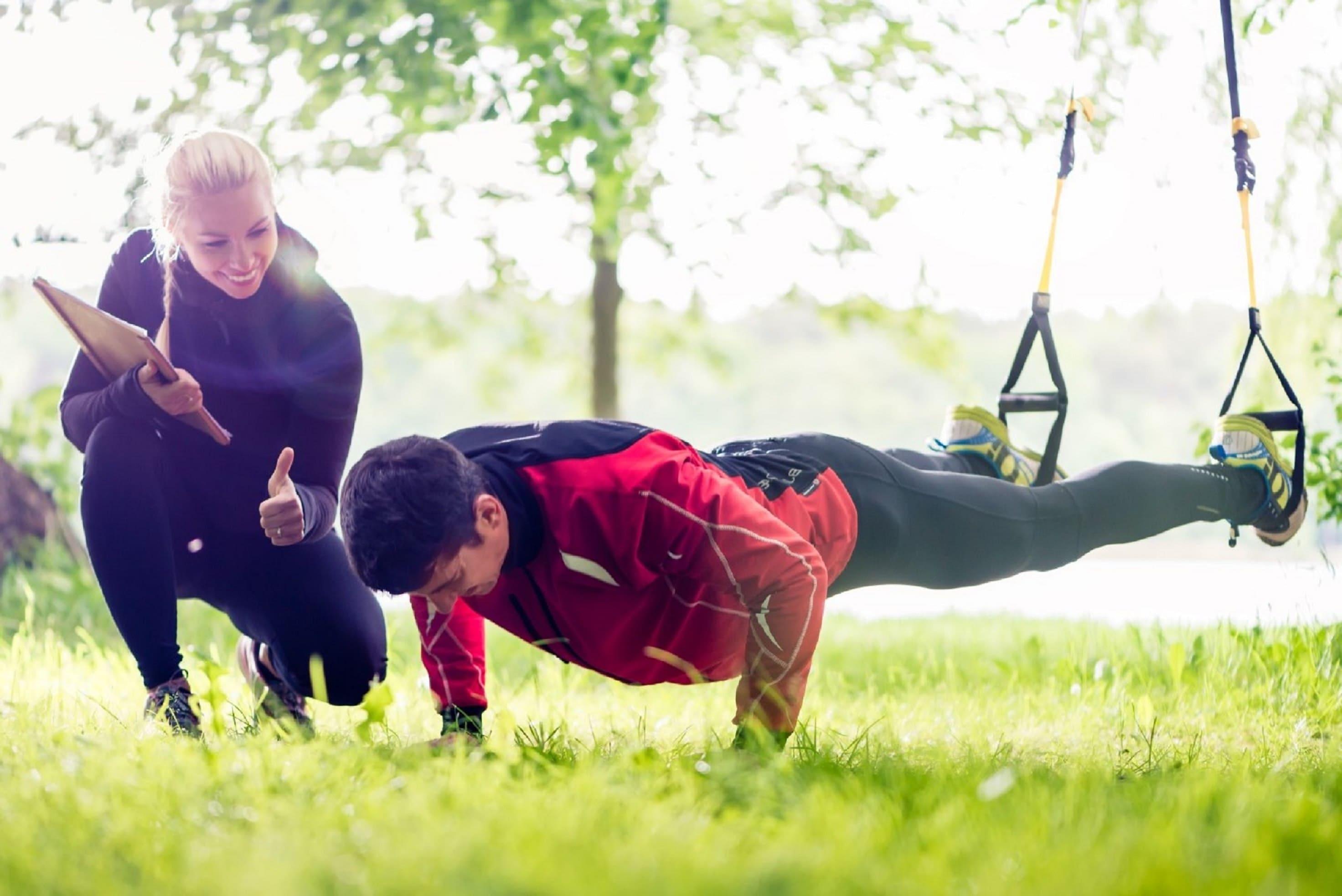 Ragazzo che si allena con personal trainer all'aperto