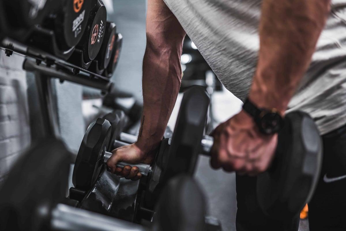 atleta si allena in palestra con manubri