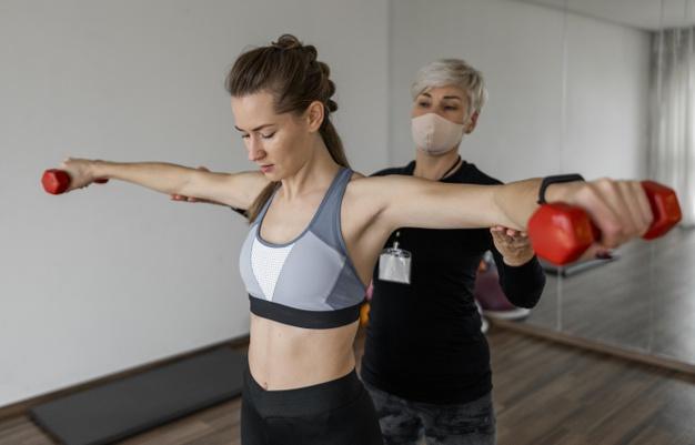 personal trainer donna segue cliente con manubri REVOO