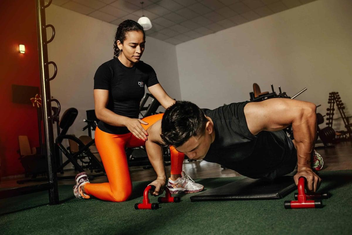 Personal trainer che allena il suo cliente