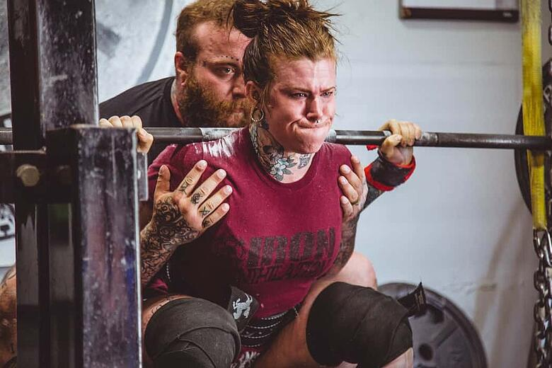 personal trainer aiuta cliente durante esercizio con bilancere