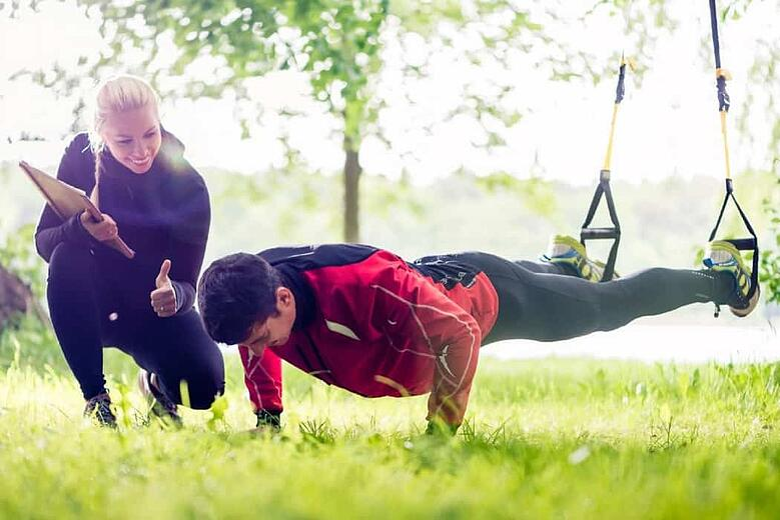 personal trainer aiuta cliente durante esercizio con TRX