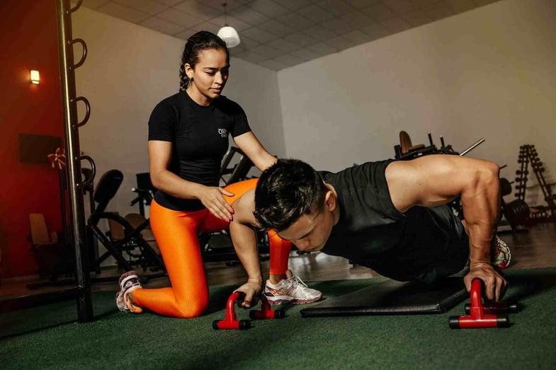 personal trainer con atleta revoo