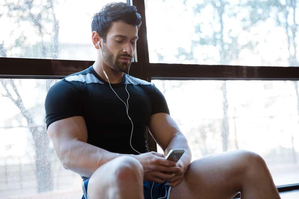 atleta controlla l'app di allenamento in palestra REVOO
