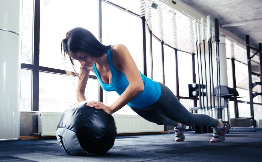 Young woman doing push up on fit ball at gym-739986-edited